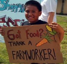 "A farm worker supporter holding a sign that says ""Got Food? Thank a Farmworker!"