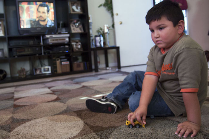 Giovany Guerra, 5, plays with his toy truck in his living room. His mother says he constantly asks her for unhealthy food he sees on television. (The Ration/ Felix Irmer)